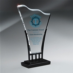 10 Clear Wellington WaveClear Acrylic Award sits atop a black iron stand. Add your color logo and text. This item can be Laser Engraved and/or Digitally Printed. Contact your salesperson for more details.New item!Call 800-830-3386 to buy now!