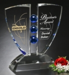 Indigo Crystal Pinion Award(This item may require extra production time. Please contact a sales rep for details.)Crystal Award with cobalt blue spheres flanked by two glass wings with ample etching space, sitting on a crystal base.New item! Also available in GREEN.Call 800-830-3386 to buy now!